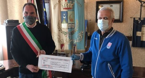 il sindaco mentre riceve la donazione dal rappresentante della Polisportiva Mogliano, il professore Mario Fenso