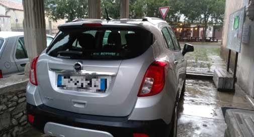 Vittorio Veneto: ripara la macchina dal maltempo e la parcheggia sotto il portico della chiesa storica, poi passa sopra la tomba antica