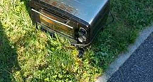 Abbandona il forno elettrico sotto il cestino pubblico